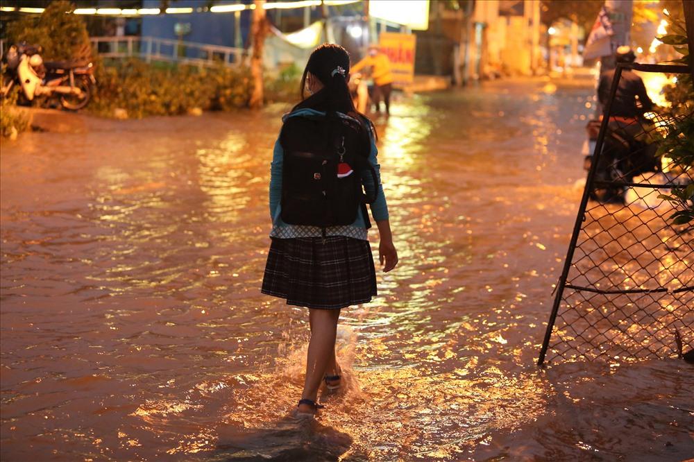 Các em học sinh phải bì bõm lội nước về nhà sau giờ học. Ảnh: Trường Sơn