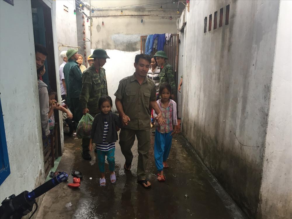 Lực lượng chức năng giúp các em nhỏ và gia đình đi tránh bão