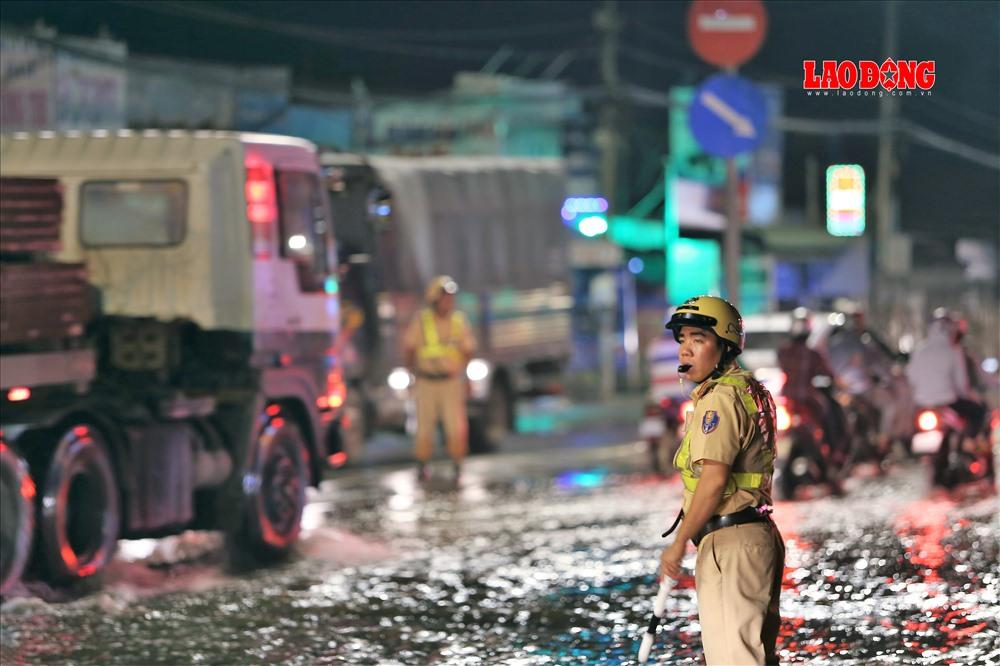Tại giao lộ, 4 cảnh sát cùng thanh niên xung phong tổ chức phân luông, điều tiết giao thông dù bên dưới dòng nước đen xì, bốc mùi liên tục trào lên mặt đường. Ảnh: Trường Sơn