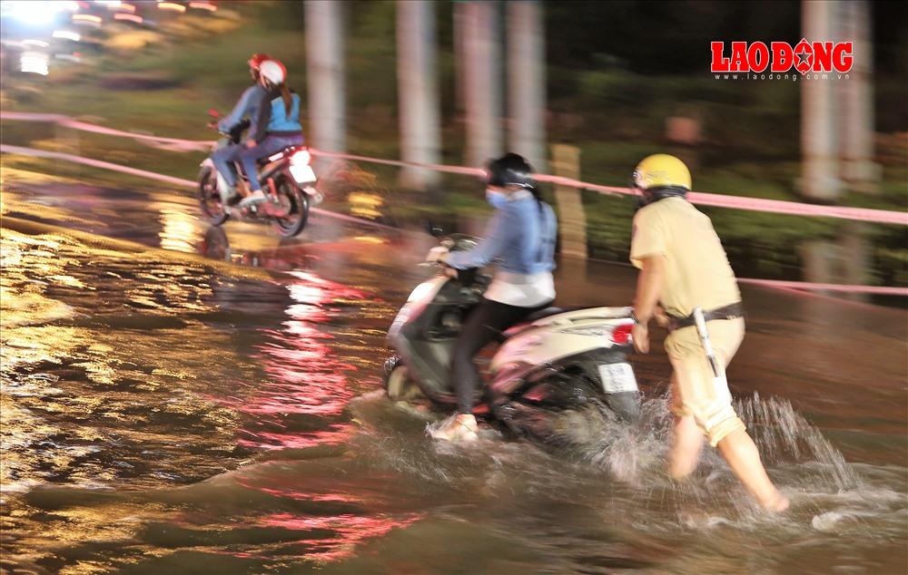 Theo ghi nhận của PV, tại điểm ngập này vào đêm 6.12 có hàng chục xe bị chết máy. Tuy nhiên, do được sự hỗ trợ tích cực từ cảnh sát nên không có người dân nào phải dầm mình trong dòng nước bẩn. Ảnh: Trường Sơn