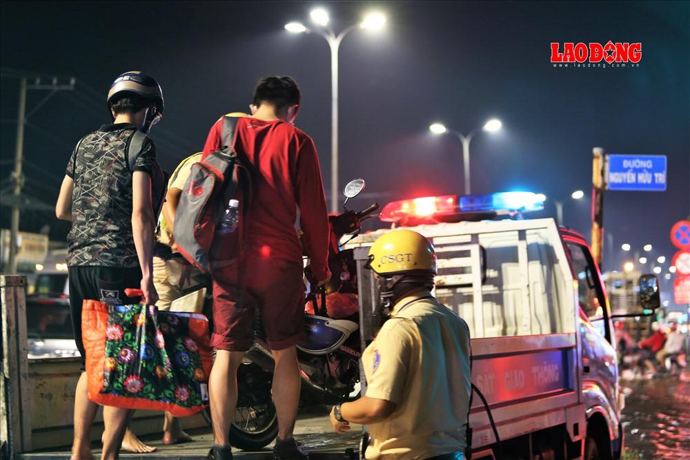 Hai bạn trẻ được CSGT hỗ trợ đưa người và phương tiện qua điểm ngập bằng xe đặc chủng của cảnh sát. Ảnh: Trường Sơn
