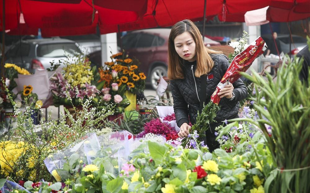 Người phụ nữ đang ngắm những bông hoa đẹp nhất mua về thắp hương gia tiên.