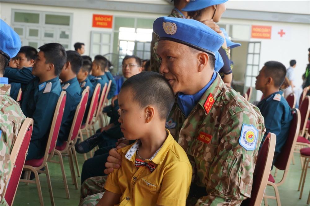 Trước giờ lên đường, một sĩ quan ngồi ôm con trai.