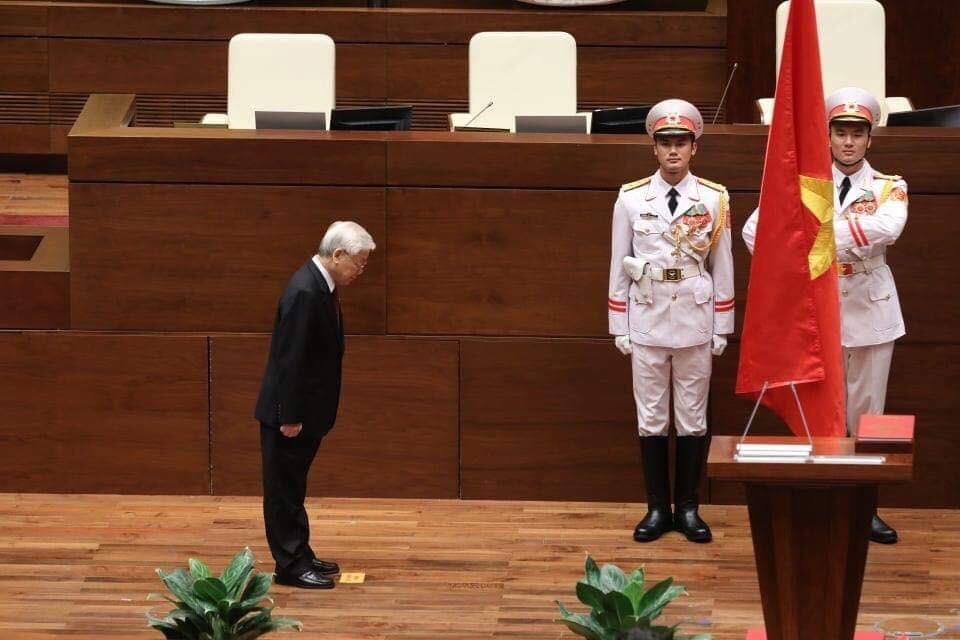 Tổng Bí thư cúi mình trước cờ Tổ quốc trước khi đứng vào bục và đọc lời tuyên thệ.