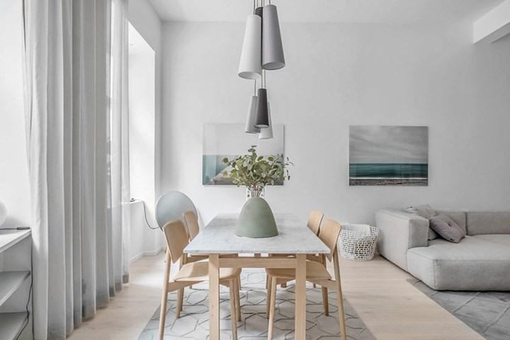 Bộ bàn ăn làm bằng gỗ sồi màu sáng tăng thêm nét ấm cúng và gần gũi trong khi mặt bàn làm từ đá thuận tiện trong việc làm sạch hàng ngày.