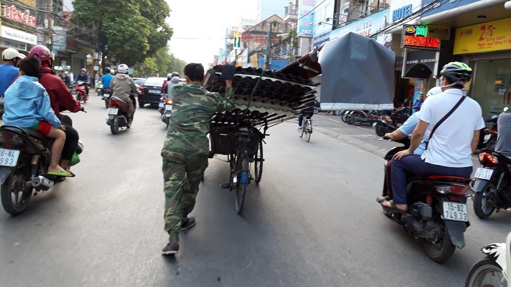 Xe chở vật liệu cao quá khổ, khiến người vận chuyển phải đẩy trên phố đông đúc.
