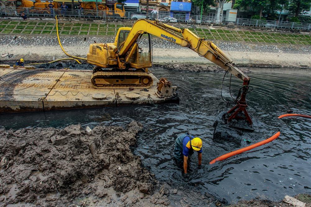 Công nhân này làm nhiệm vụ điều khiển vòi hút để hút bùn từ lòng sông lên các xe bồn trên đường.