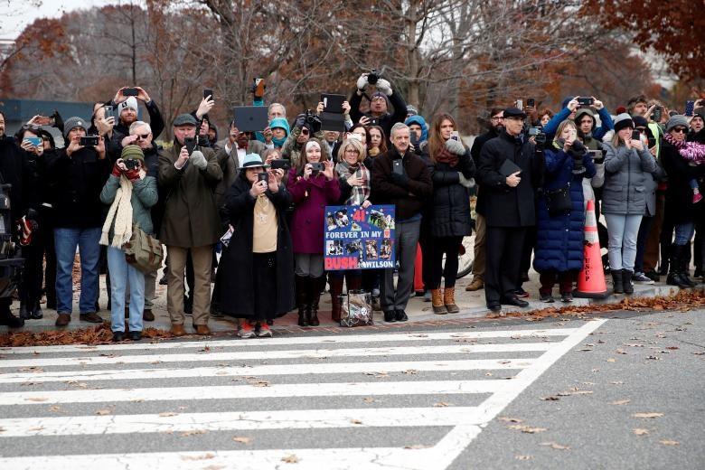 """Người dân đứng dọc ở đại lộ Pennsylvania khi đoàn xe chở linh cữu ông Bush đi từ tòa nhà quốc hội đến nhà thờ. Một người cầm bảng có dòng chữ """"Cảm ơn tổng thống thứ 41 của nước Mỹ"""". Ảnh: Reuters."""