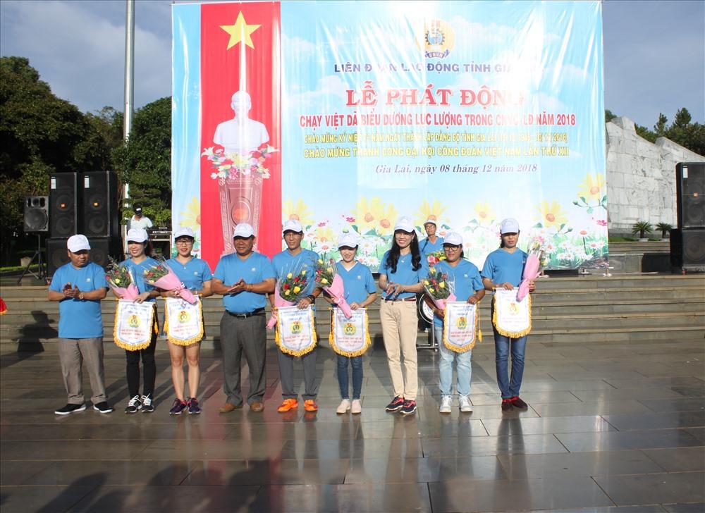 Ban Tổ chức trao tặng cờ lưu niệm cho đại diện các đơn vị công đoàn ngành tham dự chạy Việt dã, trước lúc xuất phát. Ảnh Đình Văn