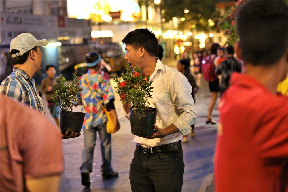 Hai thanh niên này cũng rất yêu hoa, cố gắng thu nhặt những chậu còn tươi. Ảnh: Trường Sơn