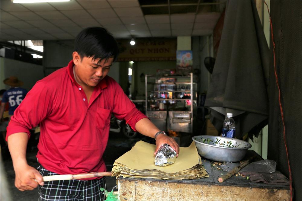 Sau khi khchs chọn loại cá ưng ý, người bán sẽ gói vào một lớp giấy bạc, sau đó phủ ngoài một lớp giấy màng vàng để tiện việc dang lên Thần Tài. Ảnh: Trường Sơn