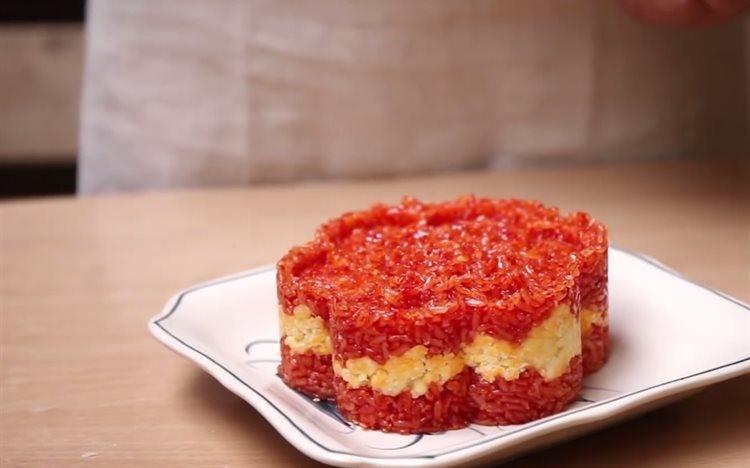 Xôi gấc: Màu đỏ tươi của xôi gấc khiến nhiều người quan niệm ăn xôi gấc đầu năm sẽ gặp nhiều may mắn. Xôi gấc được nấu từ gạo nếp trộn cùng gấc tươi rồi cho vào nồi hấp. Ảnh: cooky.vn