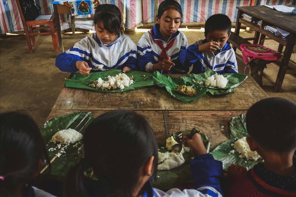 Đối với những em học sinh nhà xa thì bữa trưa được chuẩn bị sẵn cùng đồ dùng học tập để mang đến trường. Cơm cùng đồ ăn được gói gọn trong những chiếc lá dong, lá chuối, .. trở nên nguội lạnh khi để trong cặp sách vài tiếng đồng hồ. Tuy nhiên, đó vẫn là một bữa trưa đầy đủ và ngon miệng với các em. Do trường không có bán trú nên phòng học cũng là phòng ăn, bàn học cũng là bàn ăn của các em.