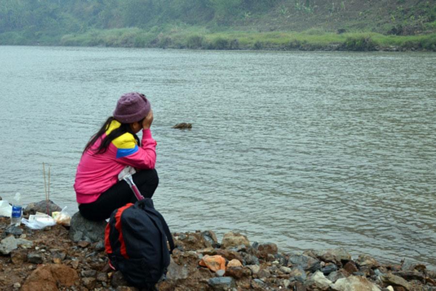 Người thân của một nạn nhân ngồi khóc bên bờ sông Hồng. Ảnh: Baolaocai.vn
