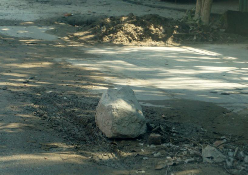 """Một cục đá được người dân đặt trên đường làm """"báo hiệu"""" các đoạn sình lầy (ảnh: Tr.L-Q.Đ)"""