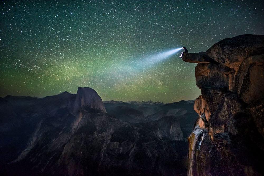 Một người đàn ông lạ mặt trong một đèn pha ở rìa Glacier Point ở Yosemite nhìn chằm chằm vào khung cảnh đáng kinh ngạc