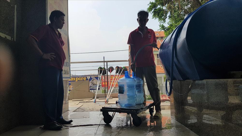 Cư dân chung cư Carina đang lấy nước để vè lau chùi nhà cửa, mong sớm được trở về. Ảnh: T.S