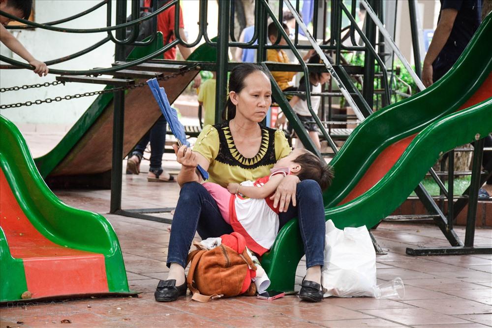 Thời tiết nắng nóng, người phụ nữ mệt mỏi chờ đến lượt cháu mình khám.