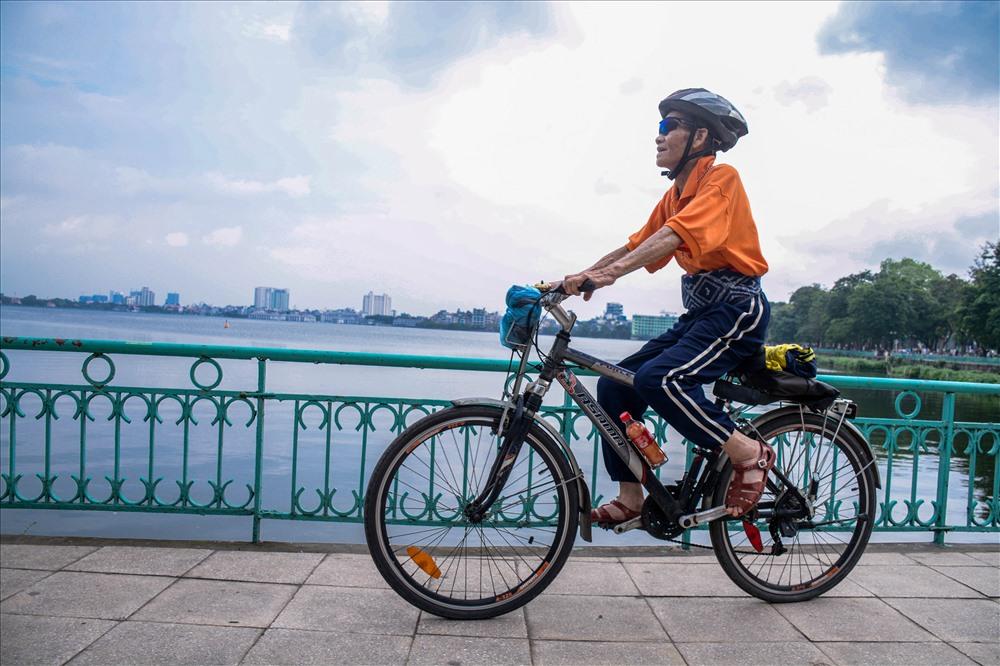 """Ông Nguyễn Xuân Vũ (82 tuổi) chia sẻ: """"Tôi là thành viên của đoàn xe đạp thể thao xuyên Việt. Nhiều chuyến tôi đi khắp các cánh cung phía Bắc, vào miền Trung thậm chí cả miền Nam. Vì hồ Tây không khí tốt lại có nhiều người cũng đi xe đạp nên tôi hay đến đây để tập thể dục. Đạp xe như một niềm đam mê rồi. Ở nhà tôi mỗi con, cháu đều có một chiếc xe đạp."""""""