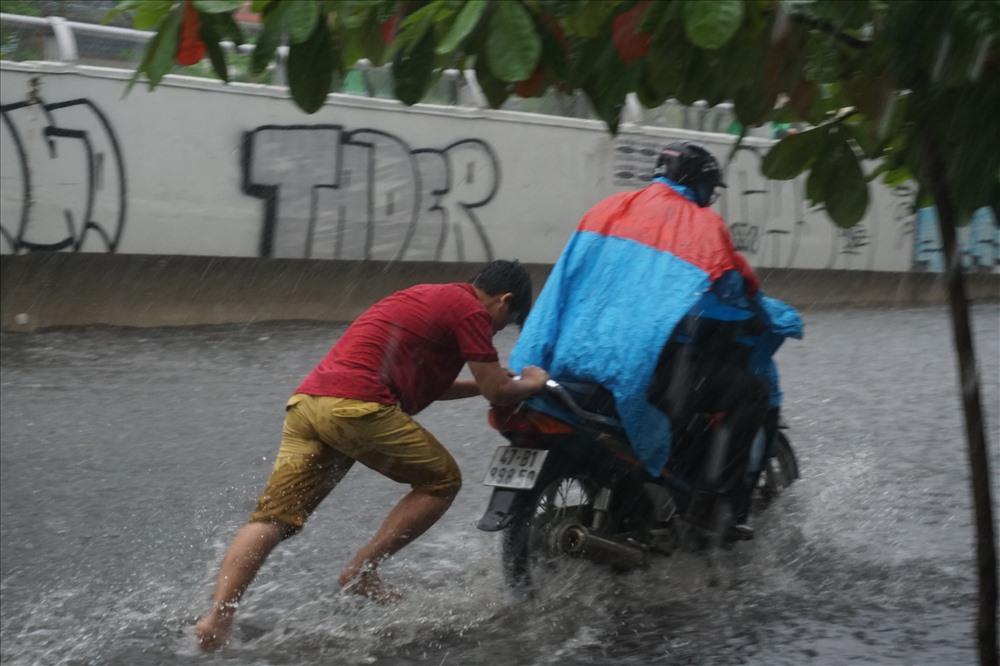 Một thanh niên sống gân đó ra đường đẩy xe chết máy giúp người dân.