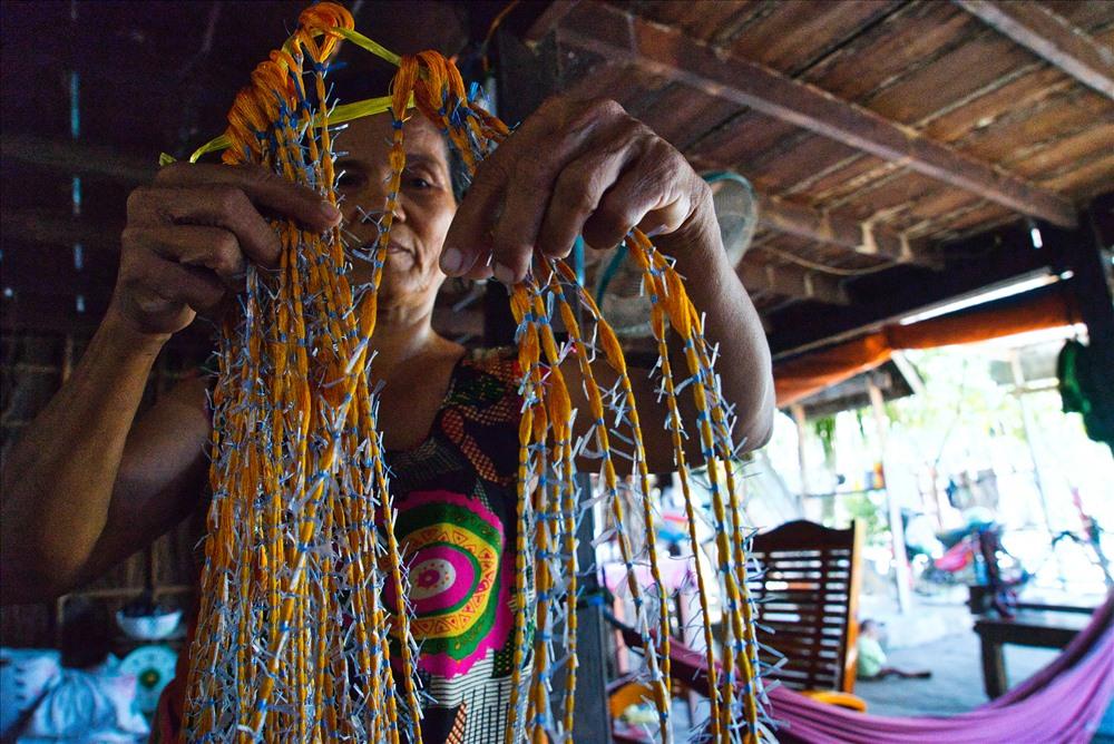 Người thợ dùng những sợi nylon buộc từng đoạn chừa lại một số đoạn theo ý tưởng rồi nhuộm.
