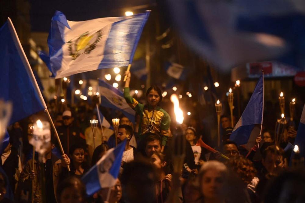 Người dân vẫy cờ trong lễ tưởng niệm cho các nạn nhân của vụ phun trào núi lửa Fuego. Ít nhất 110 người đã tử vong trong thảm họa này. Ảnh: Edwin Bercian/EPA