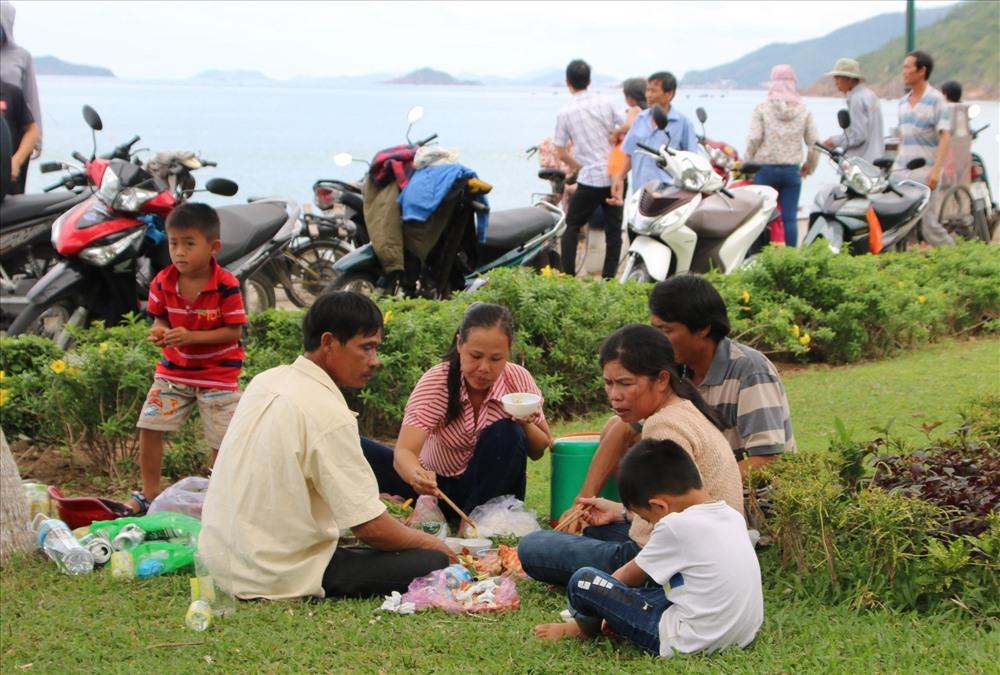 Những gia đình ở xa, họ tổ chức ăn uống, vui chơi dưới những tán cây ven biển nơi đây. Ảnh. Đ.Phùng