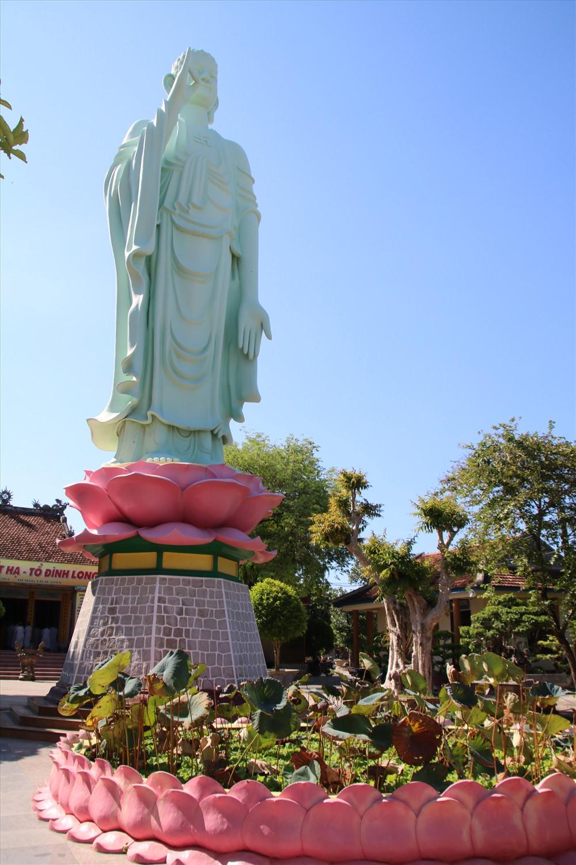Tượng được xây bằng đá xanh đặt trên đài sen, phía trước là hồ sen. Ảnh: Đ.Phùng