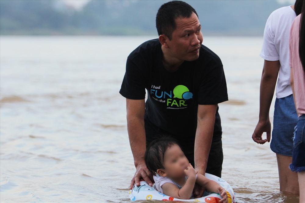 Trẻ nhỏ được trang bị phao và bố mẹ luôn theo sát bên cạnh.