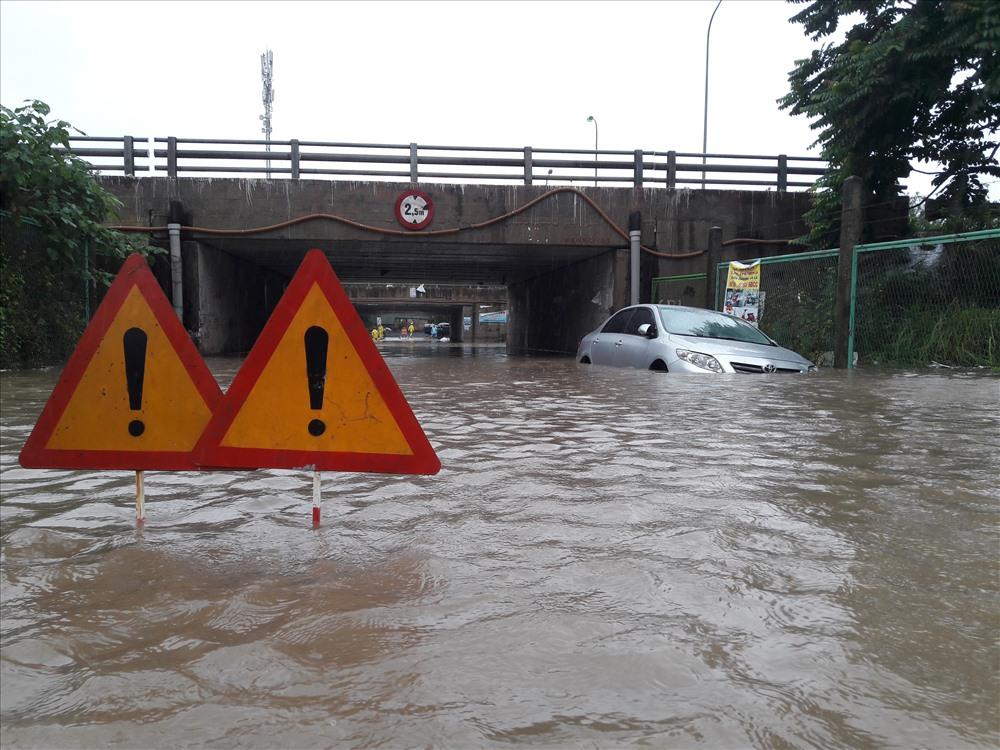 """Mặc dù nước sâu đến lưng sườn xe nhưng nhiều chiếc ô tô vẫn """"gồng mình"""" để vượt qua."""