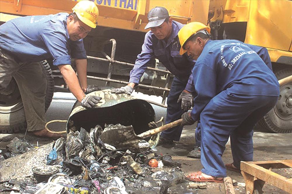 Công nhân Công ty TNHH MTV Thoát nước - Đô thị hàng ngày vớt rác từ lòng cống. Ảnh: V.A