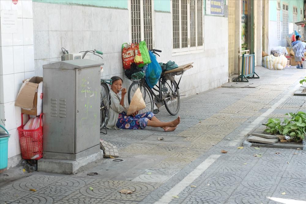 Một người phụ nữ buôn ve chai tranh thủ ngồi nghỉ trên vỉa hè để lấy sức