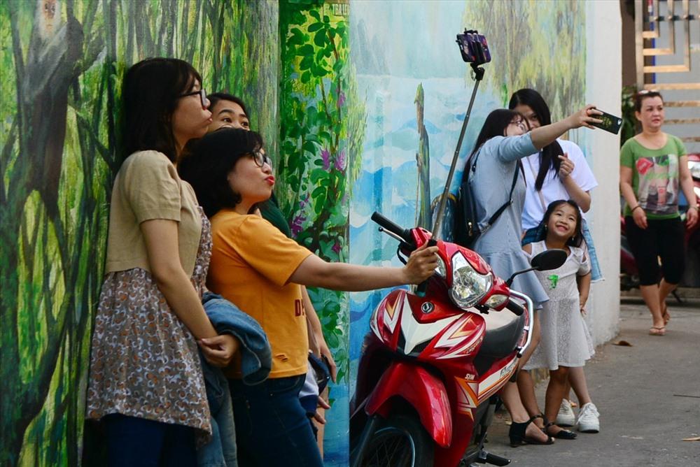 Khách ghé thăm và chụp ảnh tại hẻm bích họa Đà Nẵng trong những ngày đầu mở cửa. Ảnh: Việt Nam mới