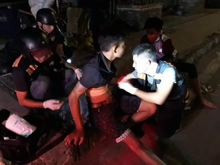 Thành viên Đội SOS tham gia băng bó vết thương cho một người đi đường bị tai nạn giao thông.