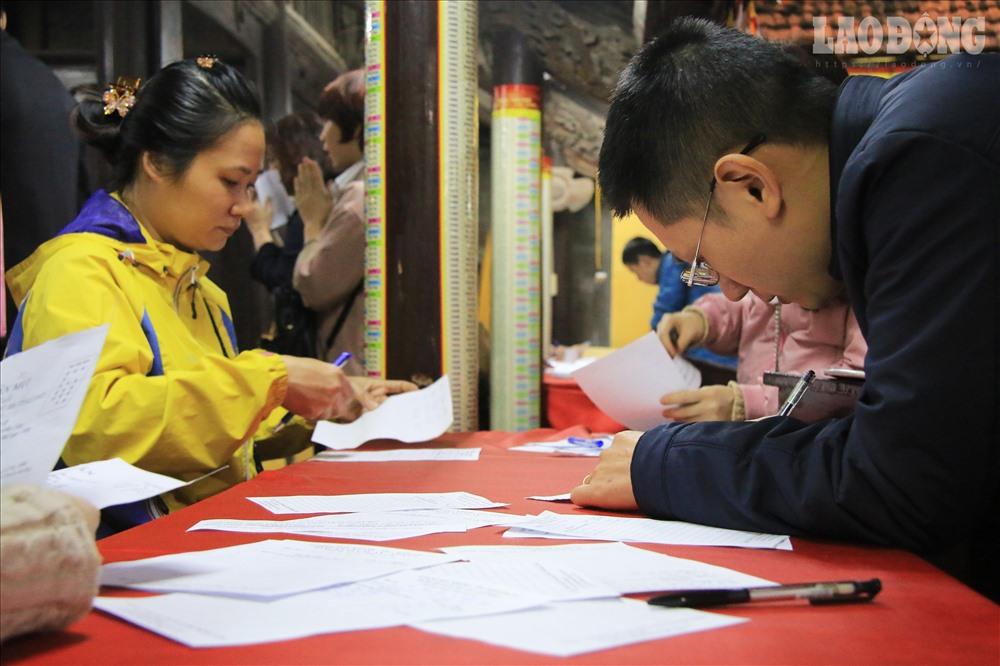 Từng người cẩn trọng theo dõi rồi đăng kí, phiếu đăng kí ghi rõ họ tên thành viên gia đình, năm sinh, tuổi và sao hạn.