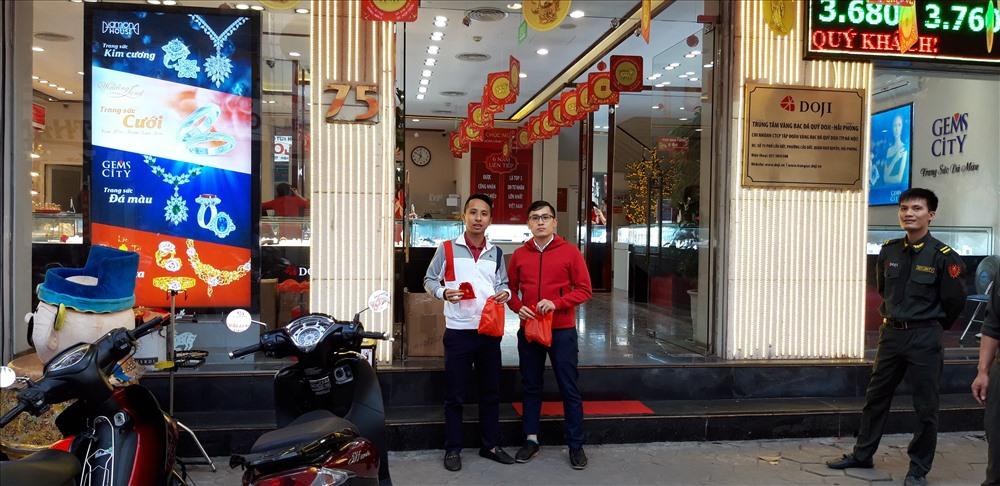 Anh Lê Minh Hoàng (SN 1989, ở phố Lán Bè) cùng em trai phấn khởi vì là khách hàng mua vàng sớm nhất, được cửa hàng tặng quà lưu niệm.