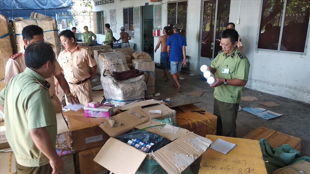 Lực lượng chức năng đang tiến hành kiểm tra các sản phẩm có trong các thùng hàng vi phạm được bốc ra từ xe tải. Ảnh: P.V