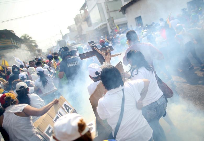 Binh lính Venezuela bắn hơi cay vào những người biểu tình tức giận vì không thể băng qua Colombia. Ảnh: Reuters.