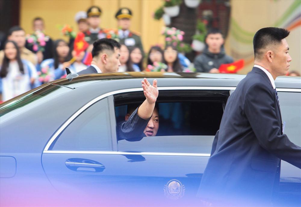 Ông Kim Jong-un vẫy tay khi trên xe di chuyển về Hà Nội.
