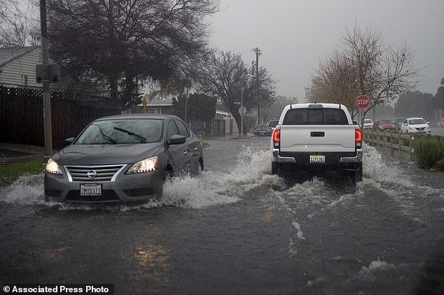 Những chiếc xe được lái qua những con đường ngập nước trong khu vực Panorama City của Thung lũng San Fernando ở Los Angeles.