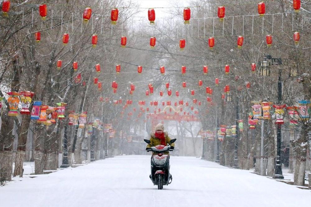 Một người phụ nữ đi xe máy qua một con đường phủ đầy tuyết được trang trí đèn lồng đỏ trước Tết Nguyên đán tại tỉnh Cam Túc, Trung Quốc. Ảnh: Reuters