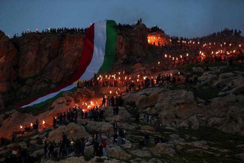 Lực lượng người Kurd dùng những ngọn đuốc thắp sáng một ngọn núi mừng lễ hội Newroz ở thị trấn Akra, Iraq.