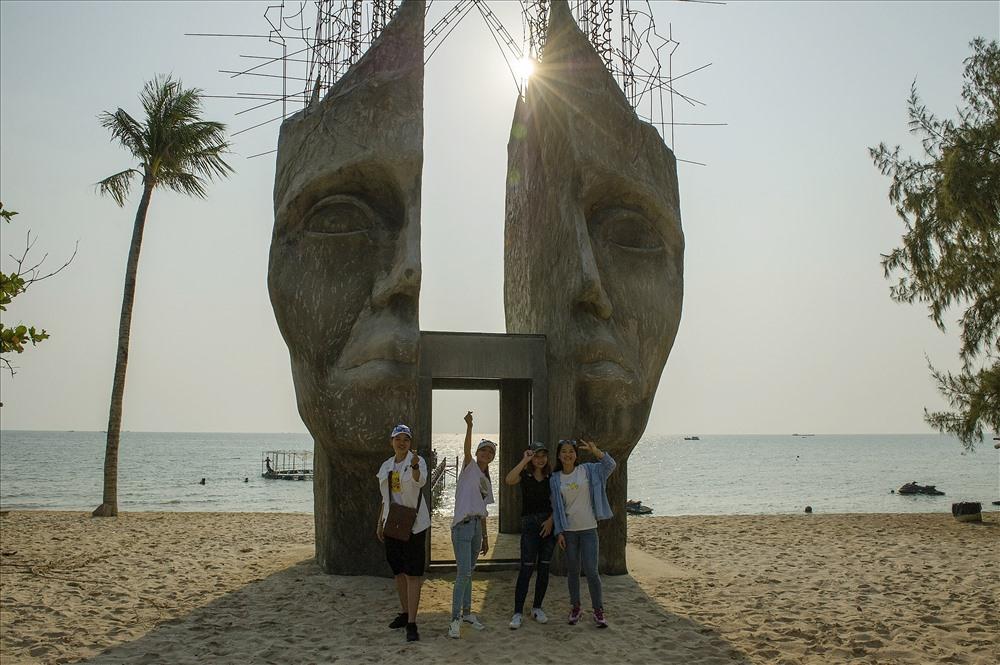 Du khách chụp ảnh tại hình tượng mặt người đá cắt đôi