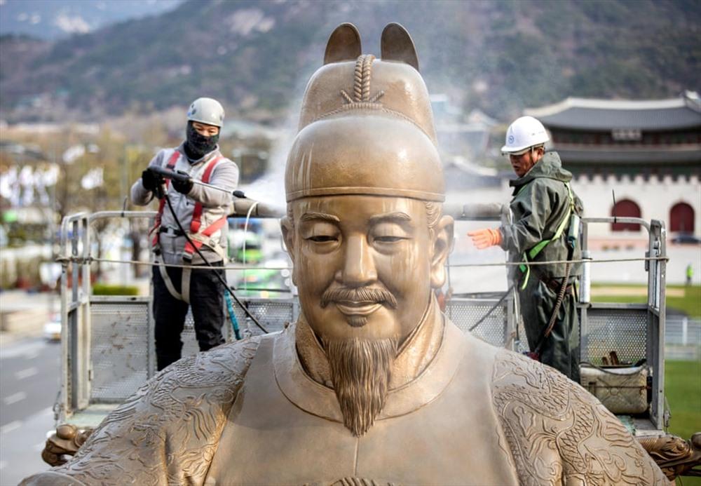 Công nhân là sạch bức tượng Đại đế Sejong ở quảng trường Gwanghwamun.  Sejong là vị vua thứ tư của triều đại Joseon, trị vì từ  năm 1418 – 1450  ( Ảnh: Yonha / EPA)