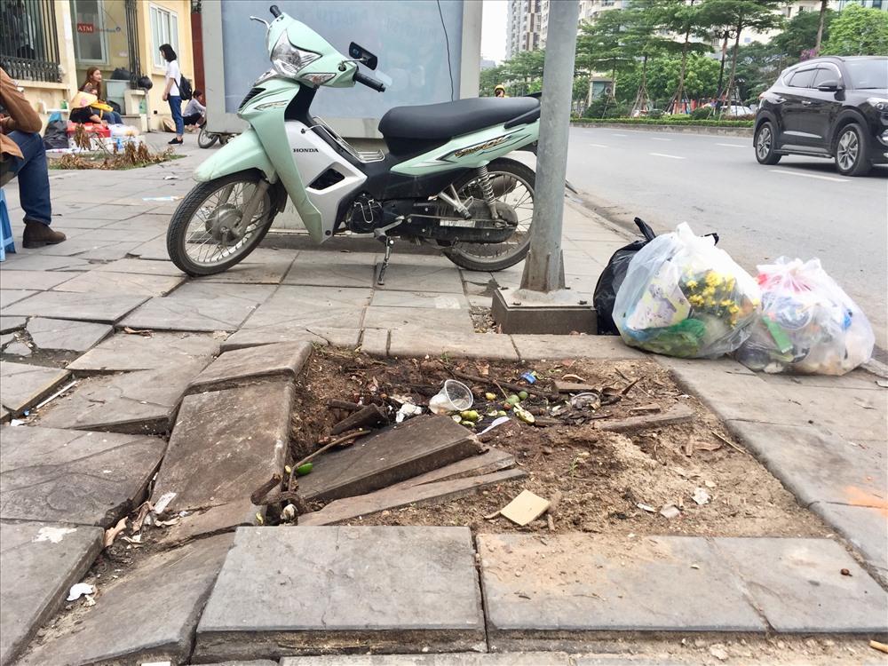 Trước cổng trường Đại học Phương Đông bên trạm xe buýt đá lát vỉa hè bong tróc thành các khoảng lớn vài mét.