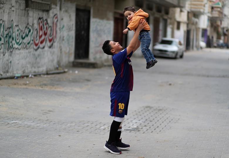 Nofal chơi với em trai của mình bên ngoài nhà của em ở trung tâm Dải Gaza