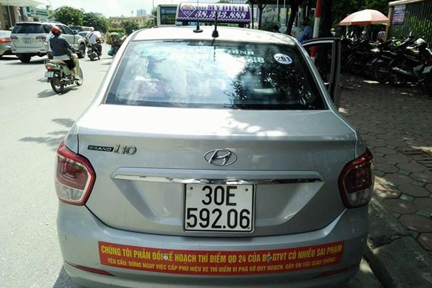 Lái xe taxi truyền thống căng băng rôn phản đối chương trình thí điểm taxi công nghệ. Ảnh: NGÔ CƯỜNG