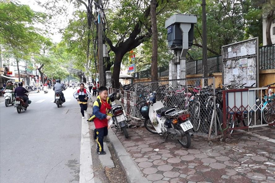 Chiếm dụng vỉa hè đường Hoàng Hoa Thám làm nơi trông xe, học sinh chỉ còn nước chạy nô dưới đường. Ảnh: TN