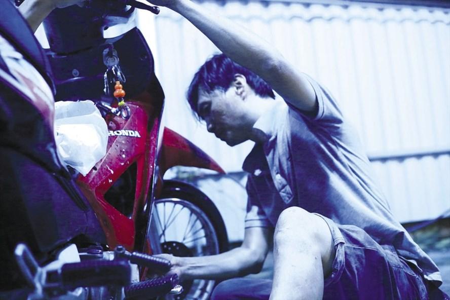 Anh Đoàn Thành Trung nhẽ nhại mồ hôi đang sửa xe bị chết máy do ngập nước.