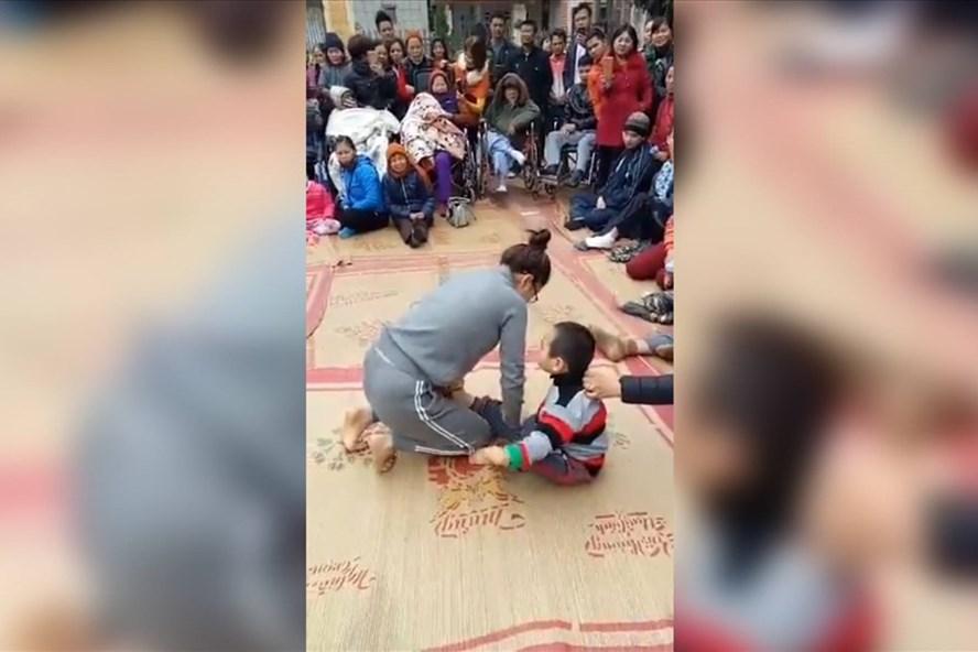 """Người được mệnh danh là """"công chúa thuốc lào"""" chữa bệnh cho một em bé bằng cách nắn chân. (Ảnh cắt từ clip)"""